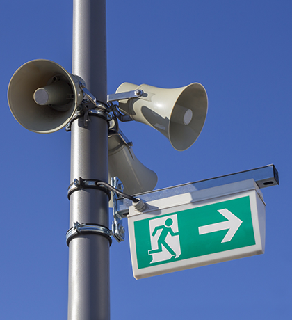 Three Megaphones and a emergency exit sign mounted to a silver pole on blue skies